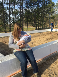 Mother from our Habitat for Humanity family holding her baby at the site of the Kingsley house construction